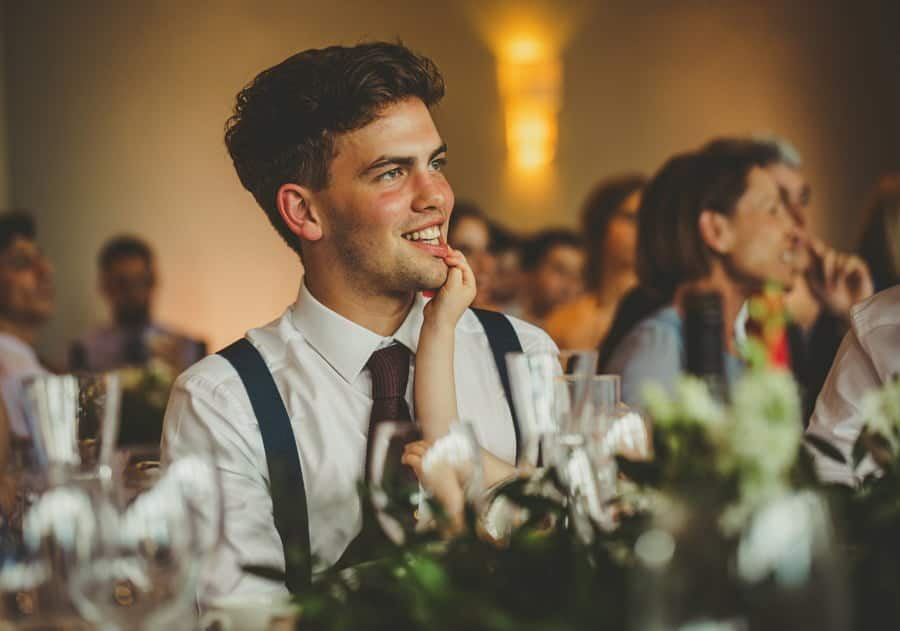 The brides brother smiles as he listens to the grooms speech