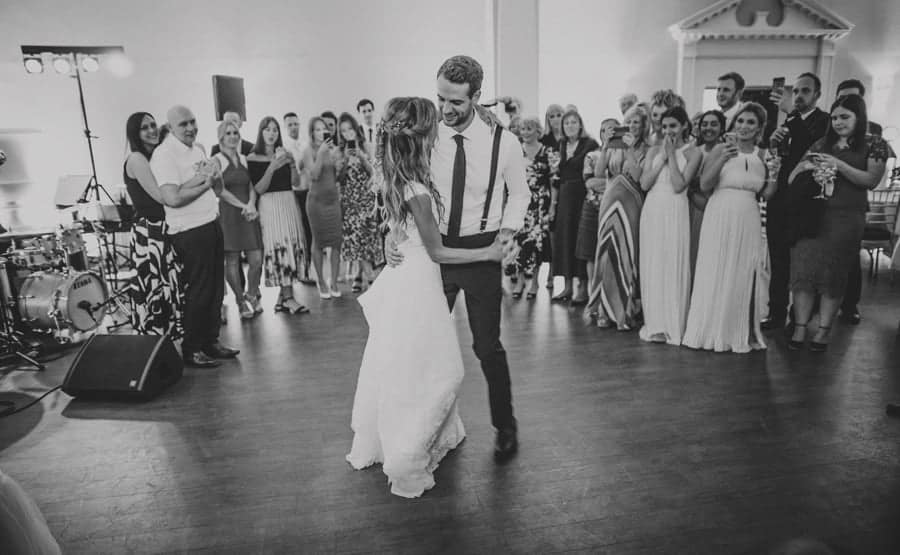 The bride and groom enjoy their first dance together as the wedding party watch at Stubton Hall