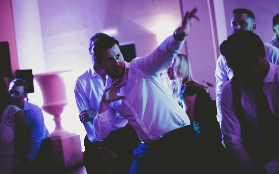 One of the ushers raises his left arm in the air on the dance floor