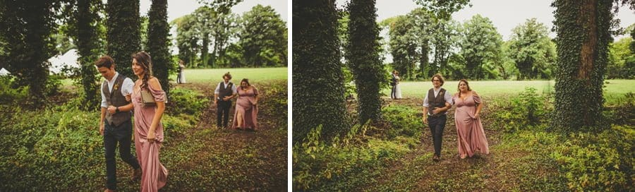 Bridesmaids and ushers walk into the woods for the wedding ceremony