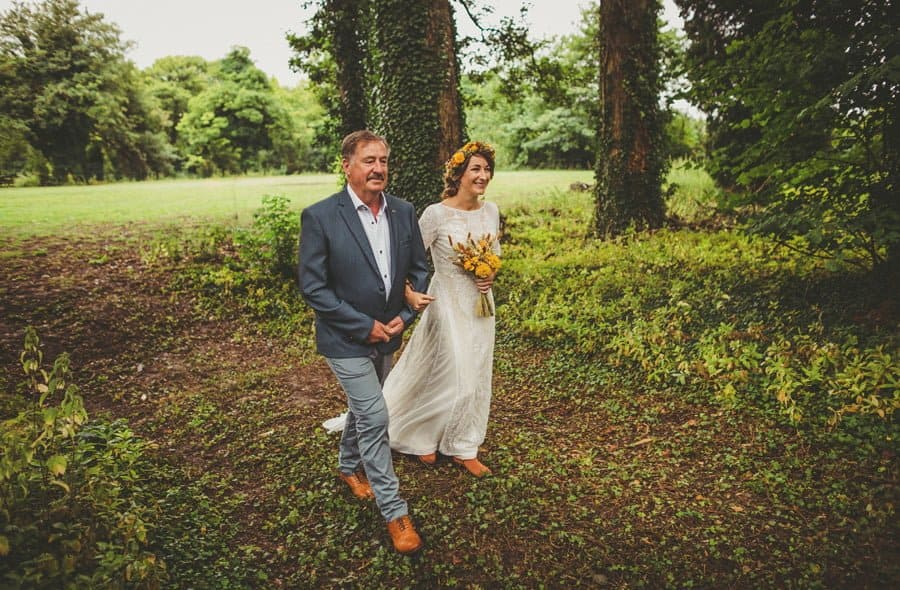 The bride and her father walk into the woods