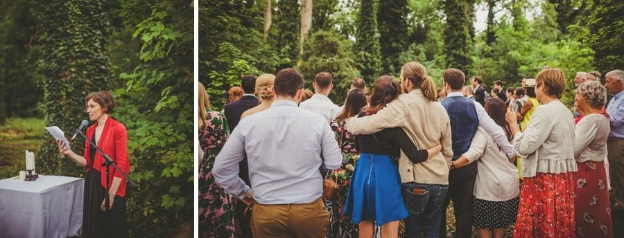 Wedding guests stand and listen to the outdoor wedding ceremony in the woods