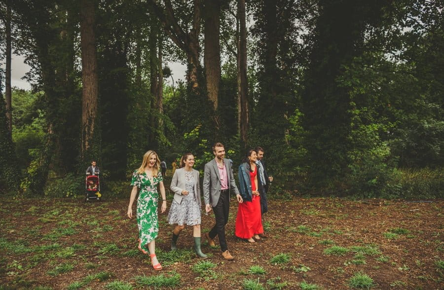 Wedding guests walk out of the woods after the outdoor wedding ceremony