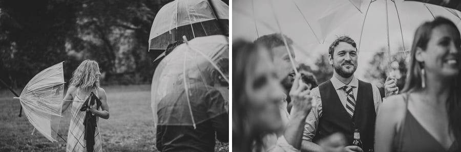 Wedding guests stand under umbrellas in the school field