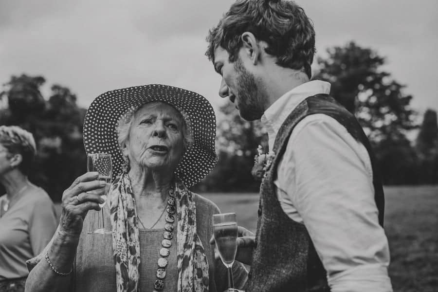 The groom and his grandmother sip champagne and talk to each other