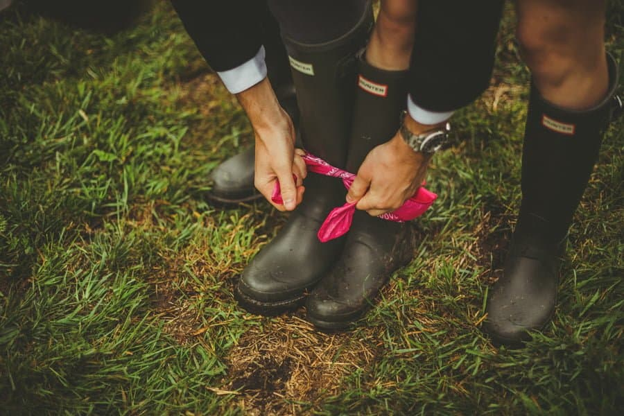 A wedding guest ties a scarf around the ankles of his partner and himself