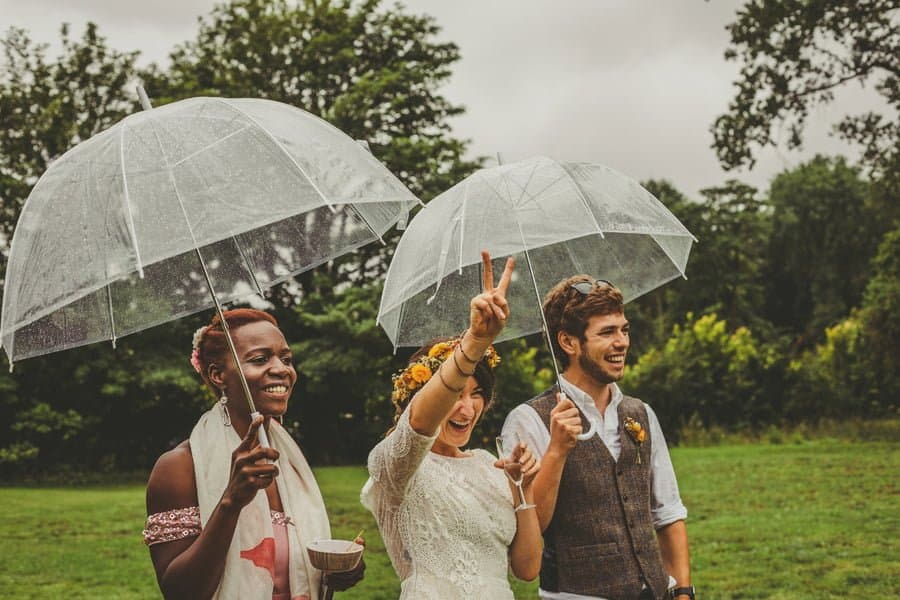 The bride, groom and one of her bridesmaids stand under umbrellas in the school field watching the games