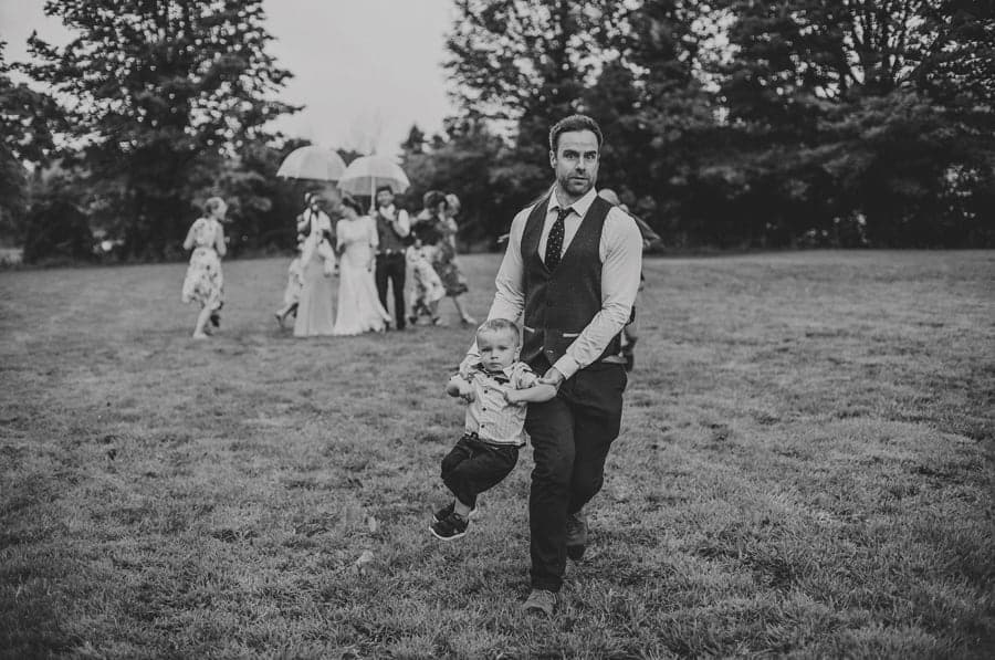 A wedding guest runs across the field with his son