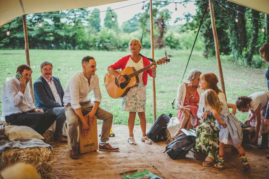 Wedding guests sing along to an Irish song under the canopy of the tent