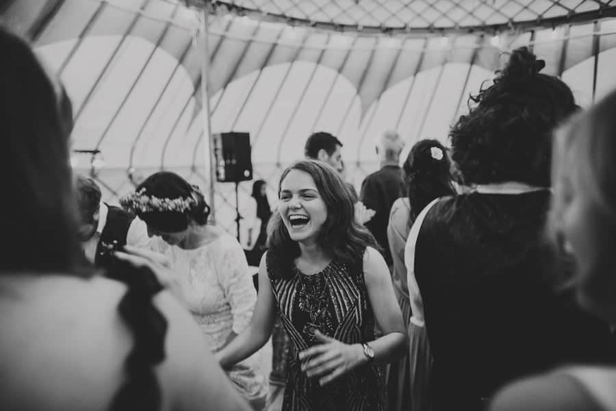 A wedding guest laughs with friends on the dance floor in the yurt