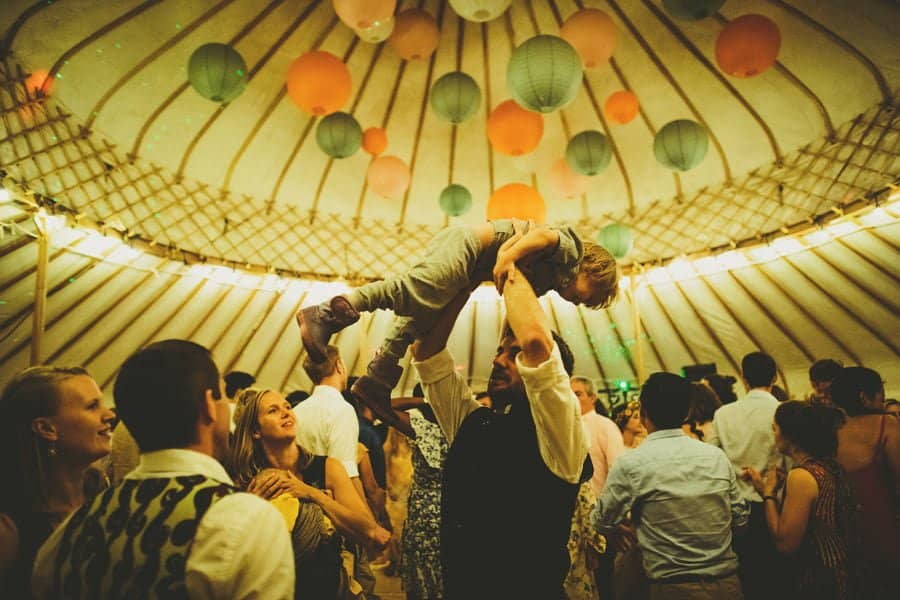A wedding guest lifts his son in the air on the dancefloor