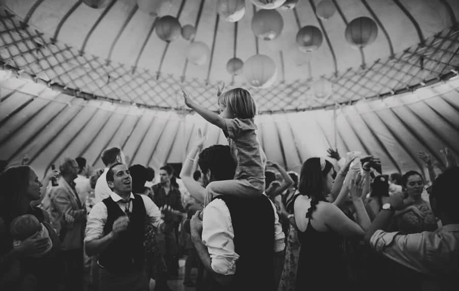 A child waves his arms in the air whilst sitting on his fathers shoulders on the dancefloor