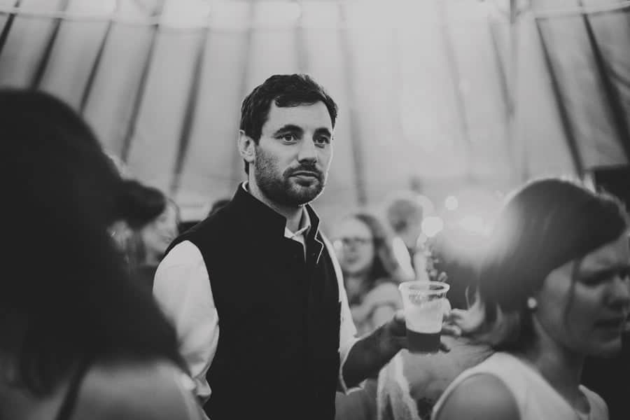 A wedding guest holds a glass of beer in the yurt