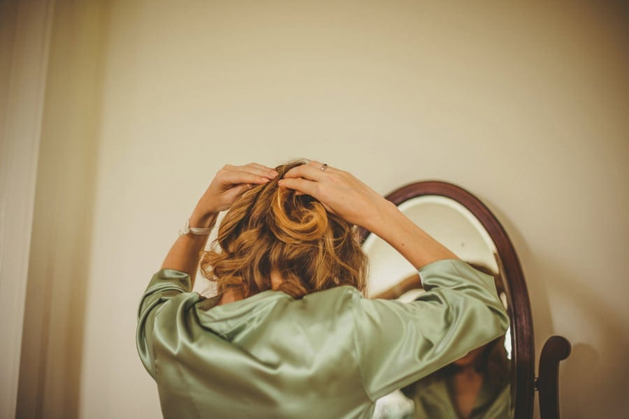 A bridesmaid fastens the back of her hair as she looks in the mirror