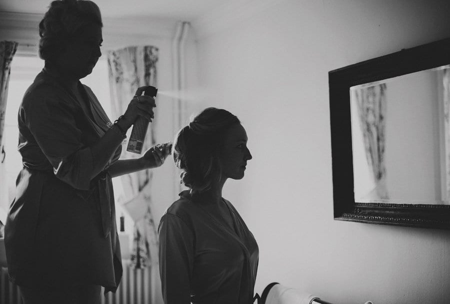 A bridesmaid stands on a chair and sprays hairspray on a friends hair as she looks into the mirror
