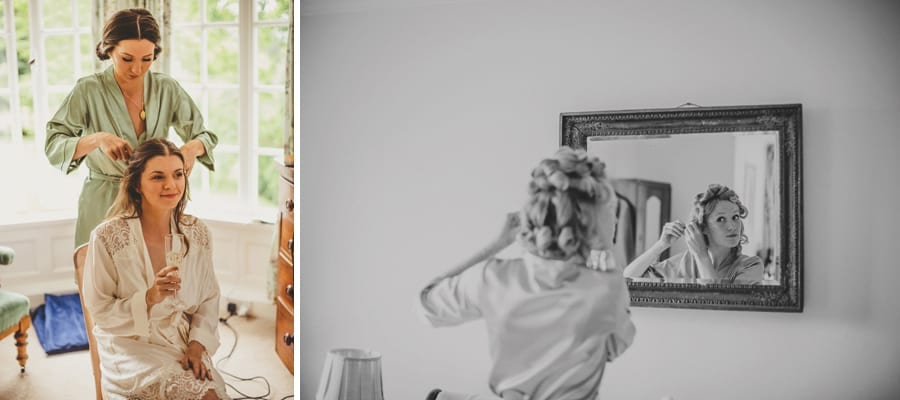 The bride sits on a chair and sips champagne and a bridesmaid takes rollers out of her as she looks in the mirror