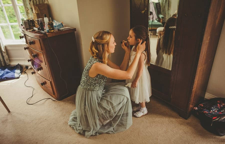 A bridesmaid puts lipstick on the flower girl next to a large wooden cupboard