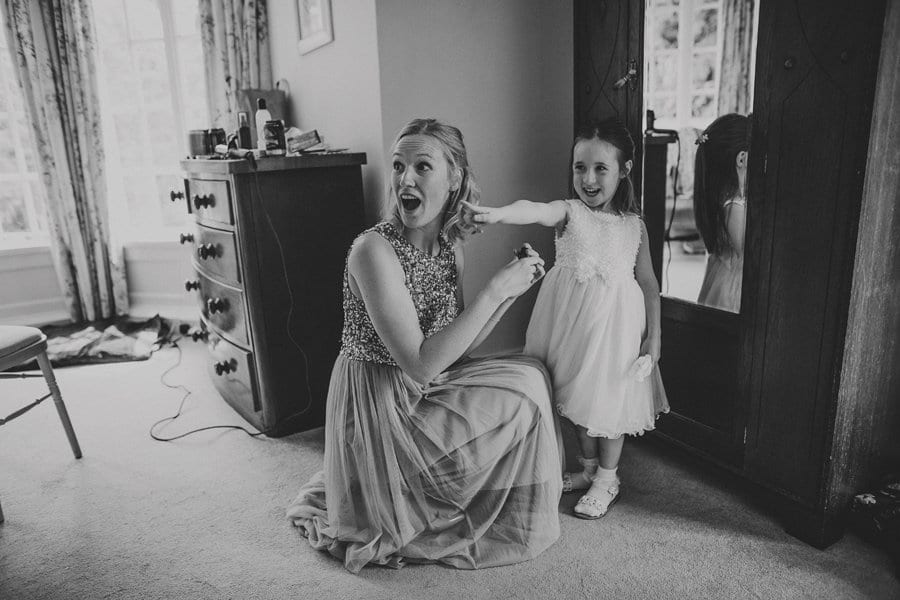 The flower girl points to her mother as the bridesmaid turns around and looks surprised