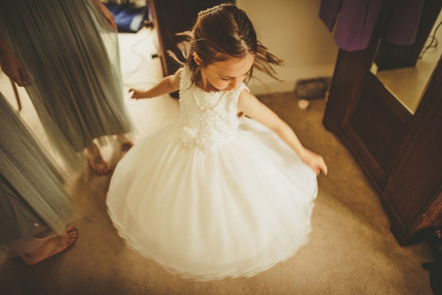 The flower girl spins around as her dress lifts up in the air