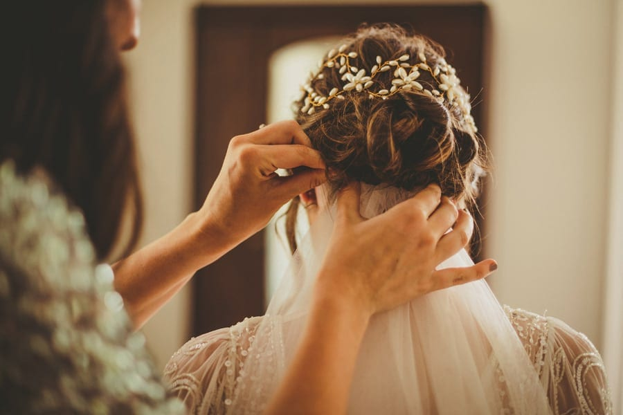A bridesmaid places the veil into the back of the brides hair