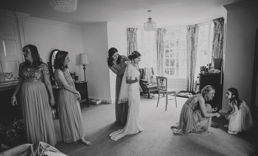 Bridesmaids getting the bride ready for her outdoor ceremony at Barley Wood house
