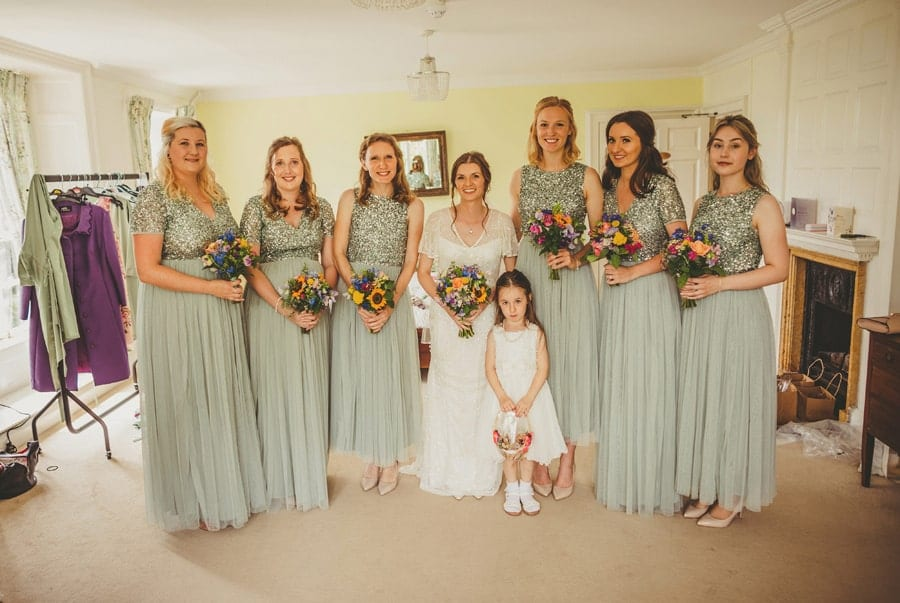 The bride, bridesmaids and flower girl pose for a photograph in the main bedroom at Barley Wood house
