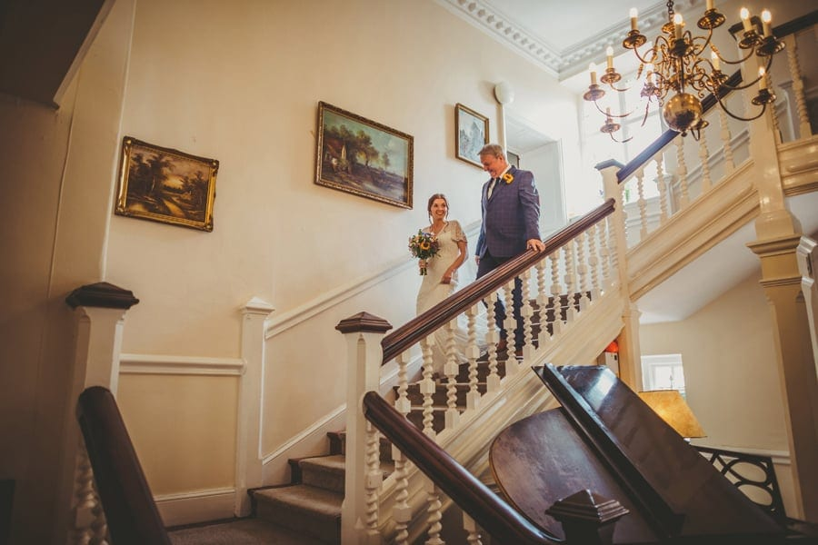 The bride and her father walking down the main staircase at Barley Wood house