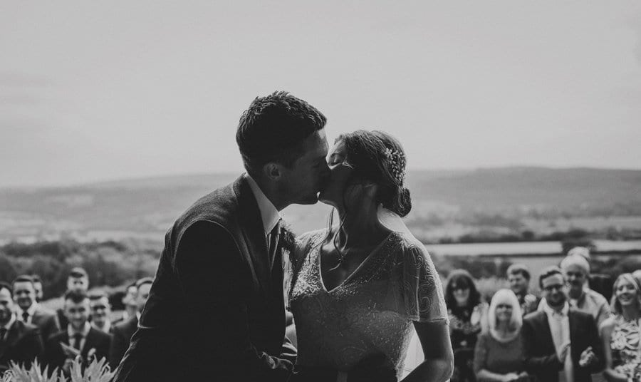 The bride and groom kiss each other during the outdoor ceremony