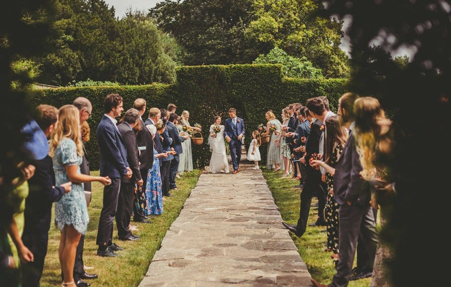 The bride and groom walk along the stone path as wedding guests throw confetti up in the air