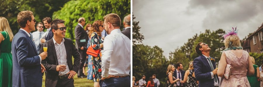 Wedding guests drinking champagne laugh and joke with one another on the lawn at the back of Barley Wood house