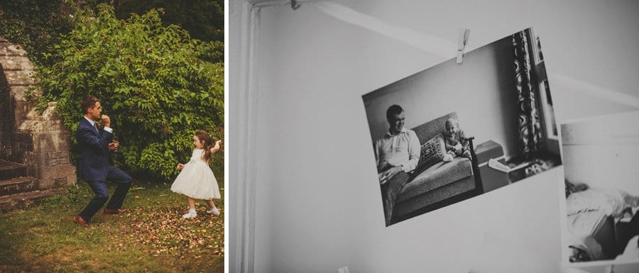 The groom plays with the flower girl and a black and white photograph hangs hangs from a ribbon