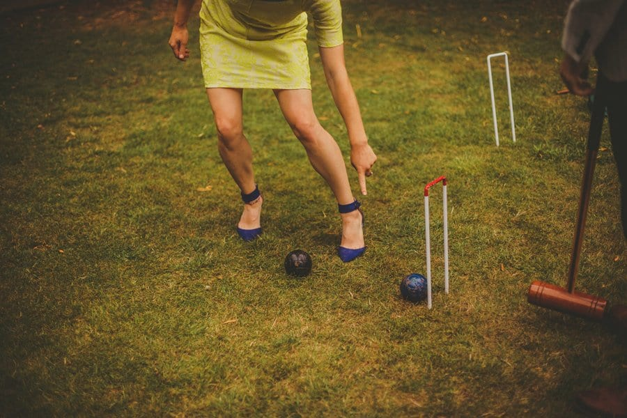 A lady points at a croquet ball as a man stands and looks on the lawn at Barley Wood house