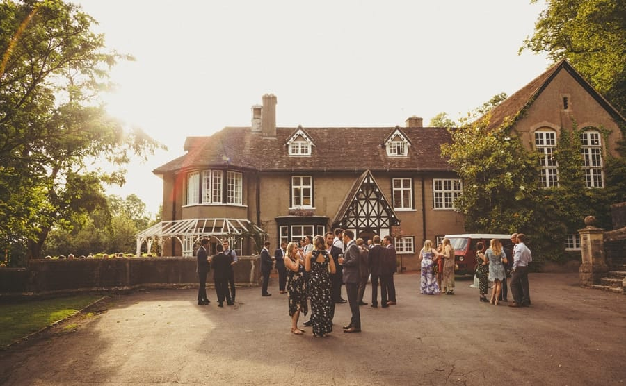 Wedding guests sipping champagne and standing at the front of Barley Wood house talking to each other