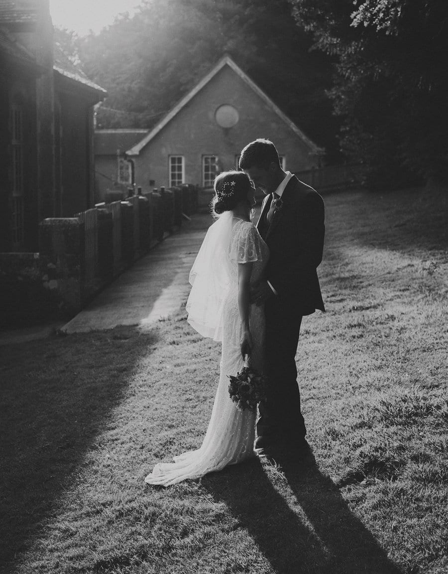 The groom looks closely into the eyes of the bride at the side of Barley Wood House in Wrington