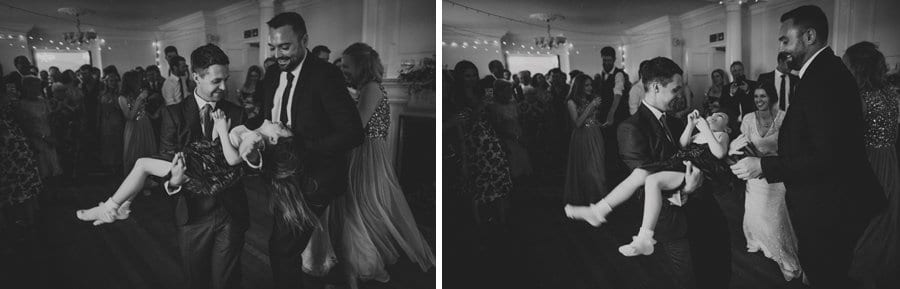 The groom holds the flower girl in his arms on the dance floor