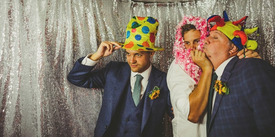 The groom and his family put hats on and pose for photographs in the photo booth