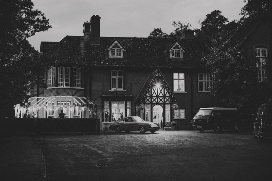 A car and a van parked outside the front of Barley Wood house late in the evening