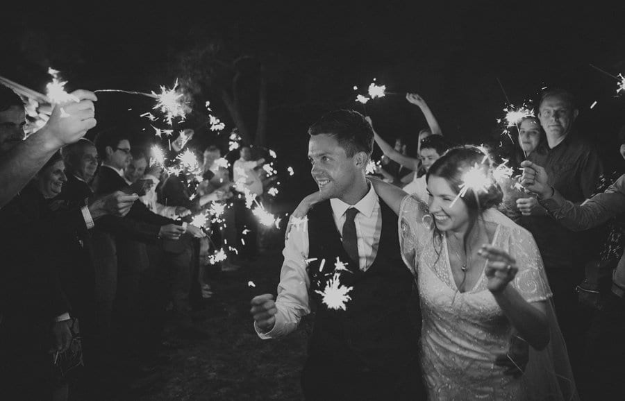 The bride and groom walk along in between the wedding guests and everybody holds sparklers together up in the air