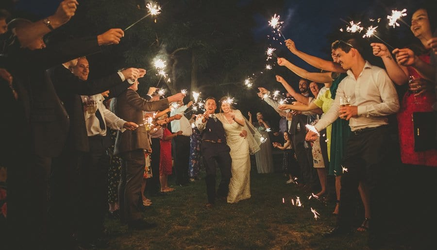 The wedding party holding sparklers up in the air