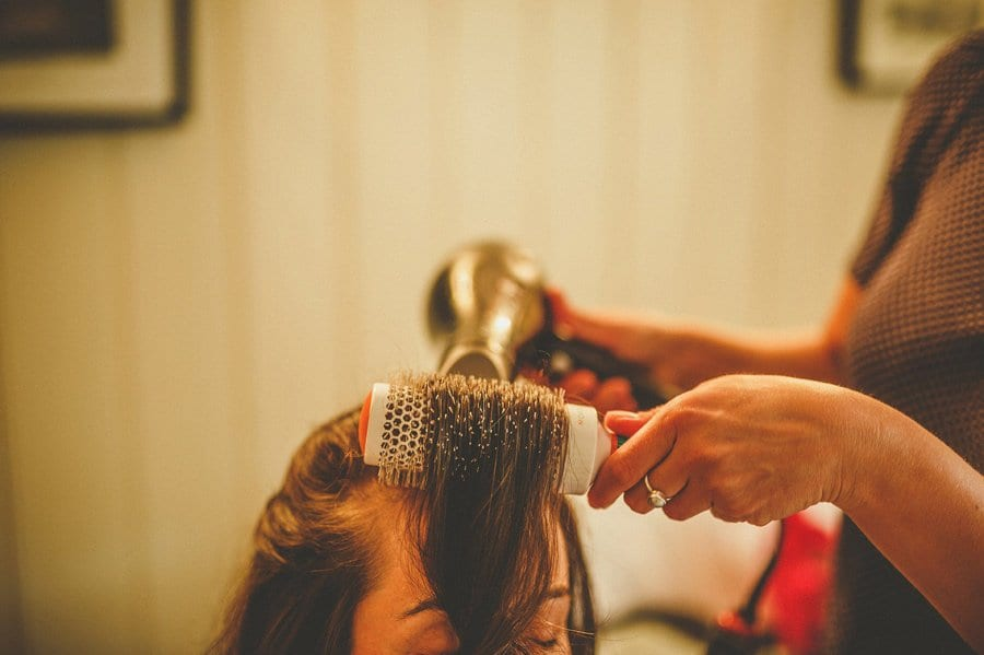A hairdresser curls the bridesmaids hair with her comb