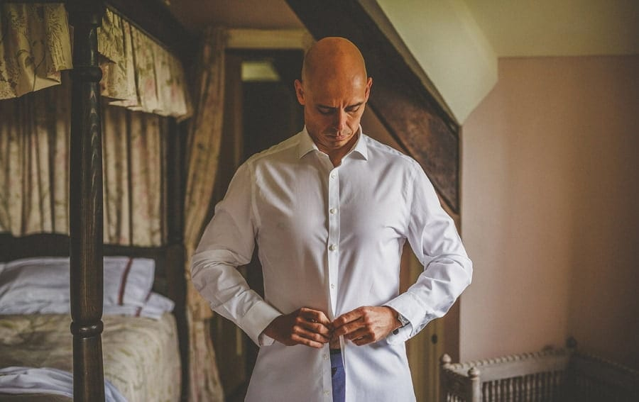 The groom fastens a button on his shirt