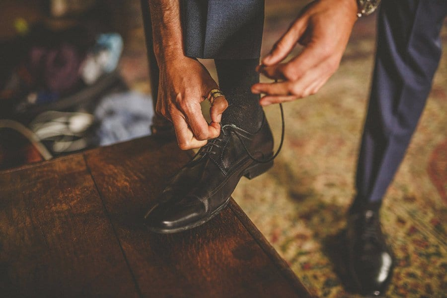 The groom ties his shoe laces