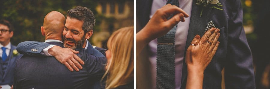 Wedding guests arriving and a lady folds a handkerchief into the breast pocket of an ushers suit