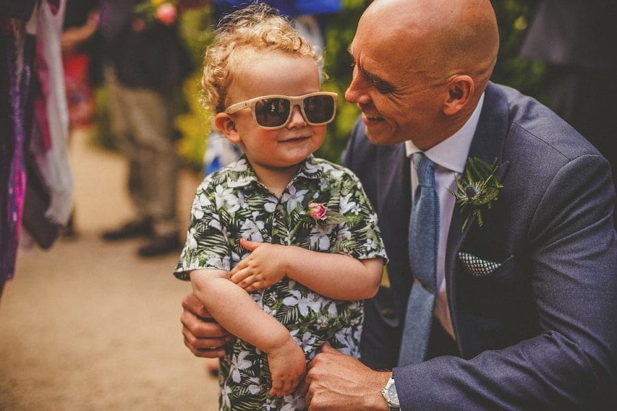The groom smiles at his son wearing sunglasses
