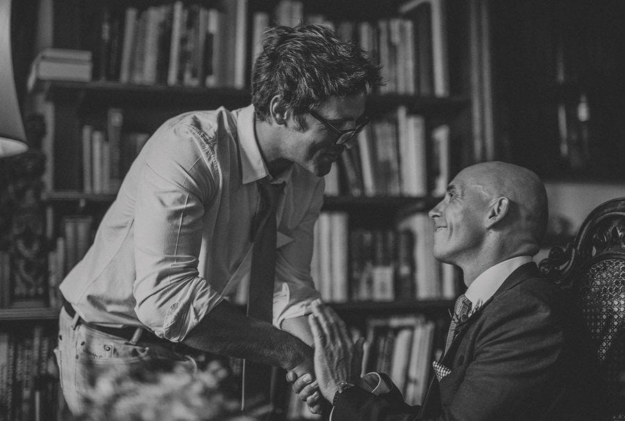 A wedding guest shakes the hand of the groom during the wedding ceremony