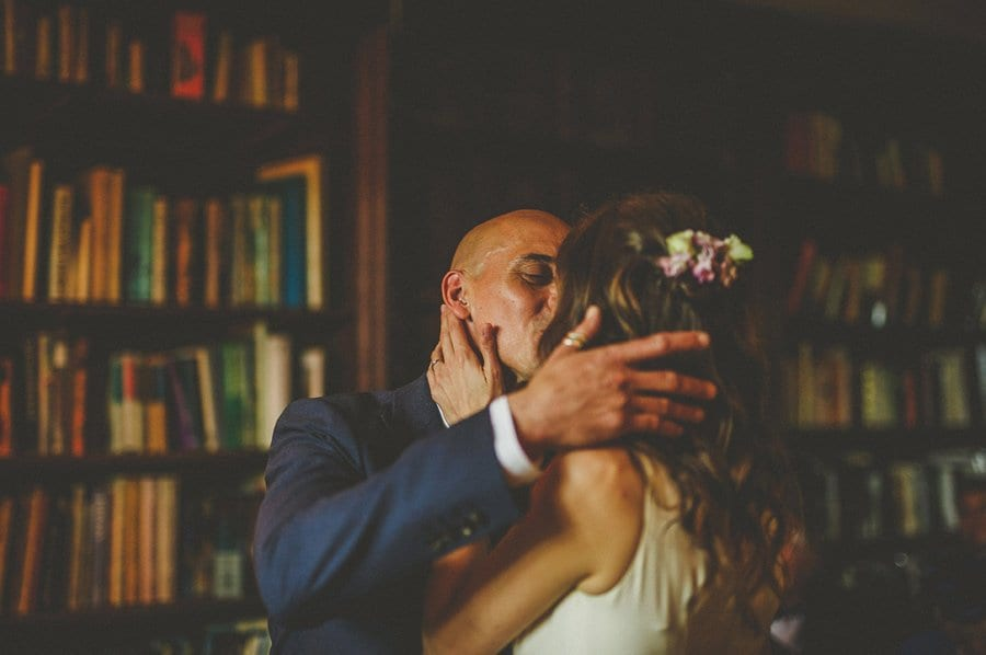 The bride and groom hold each other and kiss during the wedding ceremony