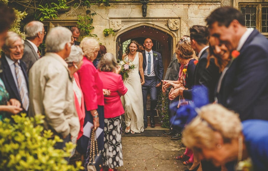 The bride and groom leave the house at Abbey House Gardens and are showered in confetti