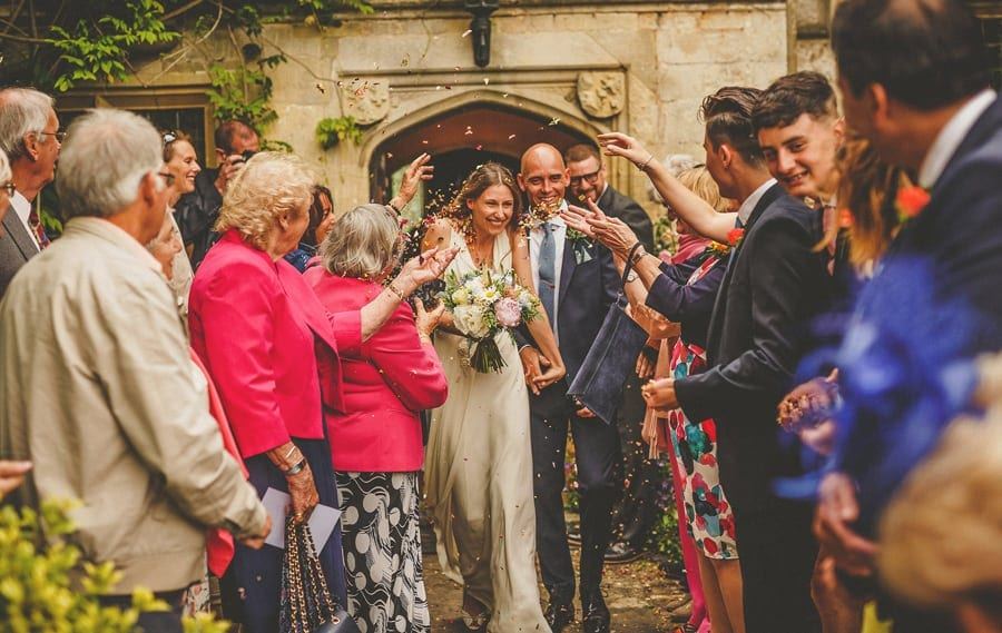Wedding guests throw confetti over the bride and groom at Abbey house Gardens