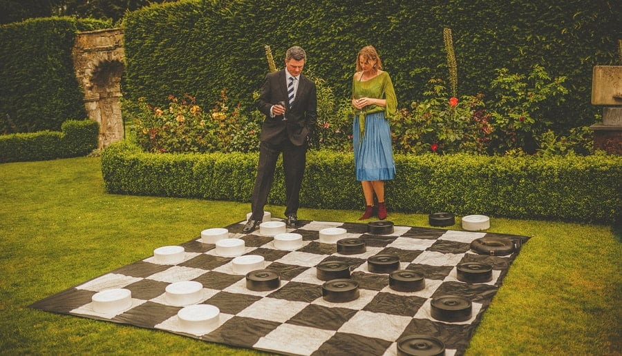 Two wedding guests look at a large draughts board on the grass at Abbey House Gardens