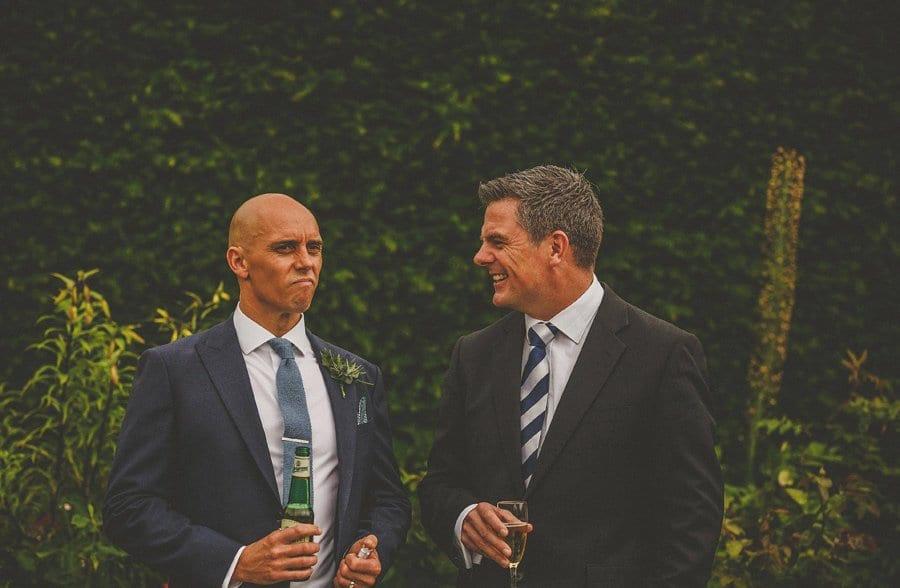 The groom talks with a wedding guest